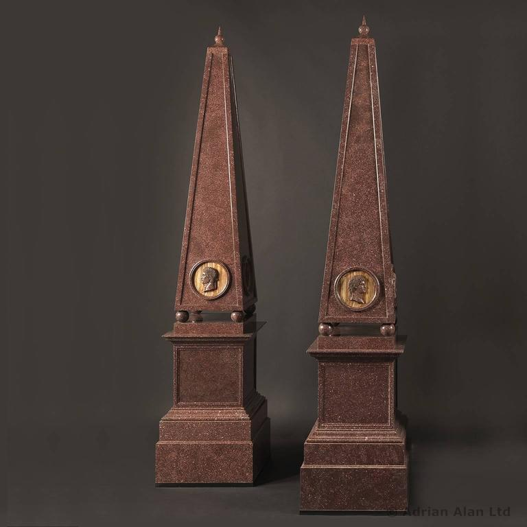 An important set of four large porphyry obelisks. Each obelisk is of square section tapering form with a spiked orb finial and embellished with carved roundels of the twelve Roman Emperors in profile. The main body is raised on ball supports putdown
