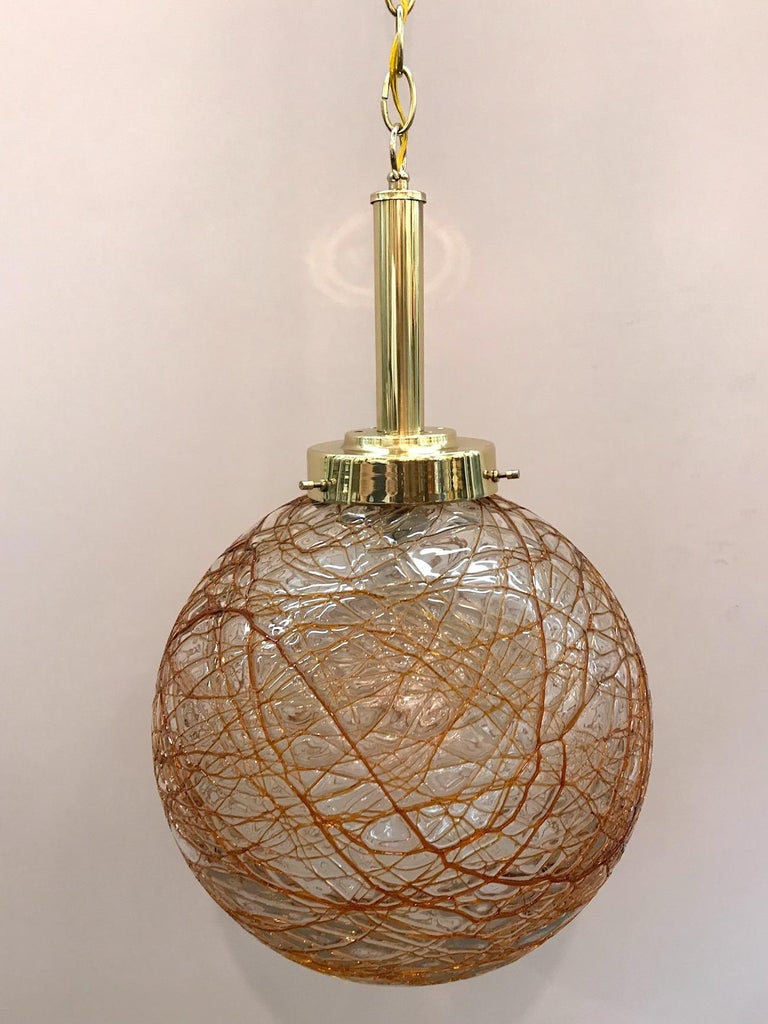 A lovely circa 1970s pendant light from Murano Italy. Globe shade of handblown clear glass with applied amber color glass splatter design. Brass mount, chain and original matching dome ceiling canopy. Diameter of globe is 12 inches. Pendant as