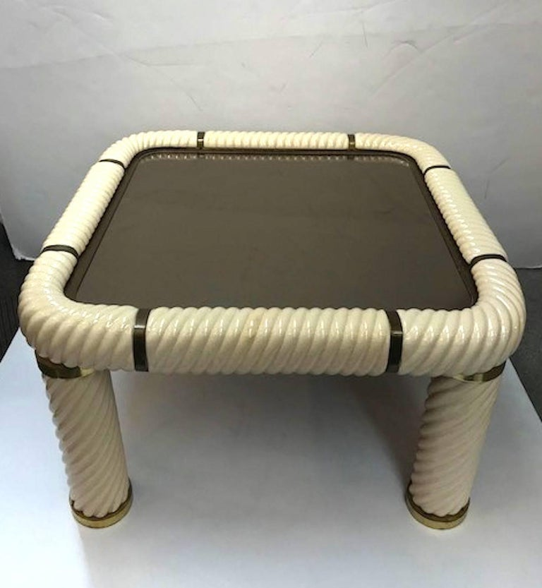 A wonderful pair of brass and ivory ceramic end or side tables with amber mirror tops by famous Italian designer Tommaso Barbi.