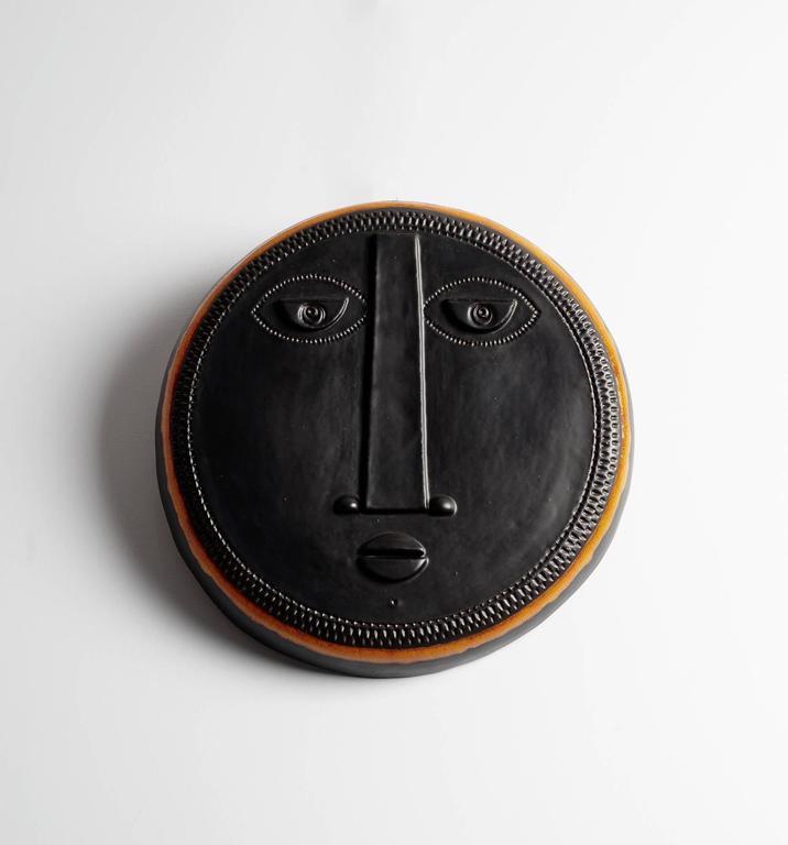 Decorative black ceramic mask with stylized face and shiny orange enamel around, creation 2017, unique piece by French ceramists Dalo.