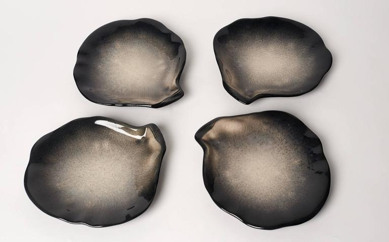 Pol Chambost (1906-1983), France.  Four black and grey plates looking like pearly sea shell.  Signed Pol Chambost, France.