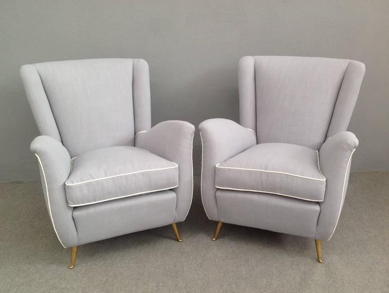 Extraordinary pair of armchairs with brass legs in the manner of Gio Ponti. Manufacturer Isa. Newly upholstered with grey and white linen.
