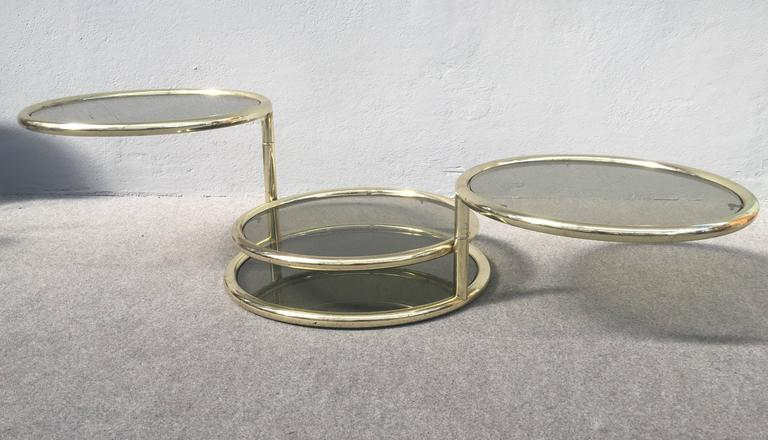 Very nice four tiers coffee table, glass and metal frame has applied brass patina. Please look at the pictures for see how you could slide the tiers. Measures max opened table cm 180.