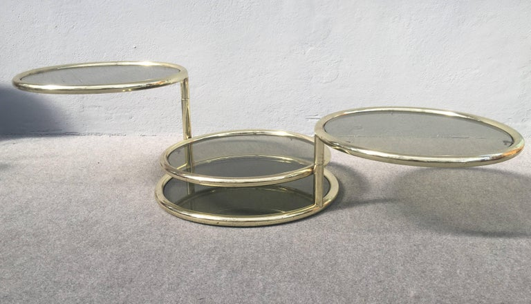 Very nice four tiers coffee table, glass and metal frame has applied brass patina. Please look at the pictures for see how you could slide the tiers.
