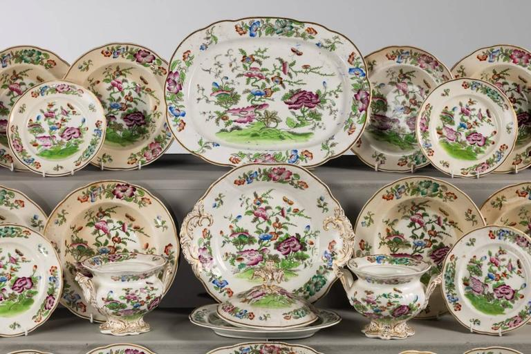 An English mid-19th century porcelain part dinner service of oriental design. With exotic flowers and foliage. 