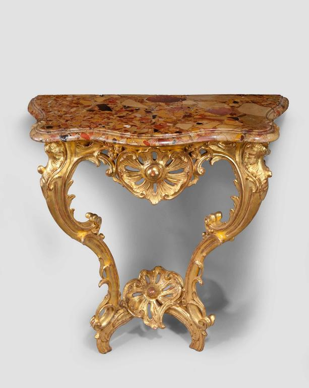 An early Louis XV Rococo giltwood console table on two elaborately carved front supports, the base with an upturned cross stretcher supporting an elaborate carved flower, well carved leaf and scroll decoration with a period marble top.
