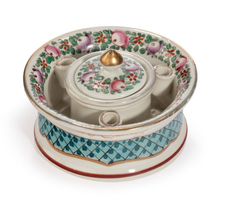 A continental porcelain inkwell retaining the liner and lid. The lid with a minor chip to the underside. The circular container also with quill holders.