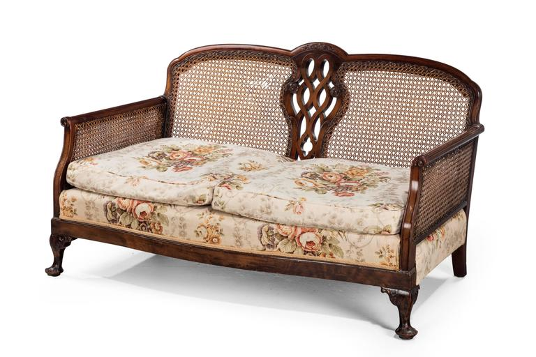 A mahogany framed bergere sofa of small proportions. With good quality original cane work to the sides and back.