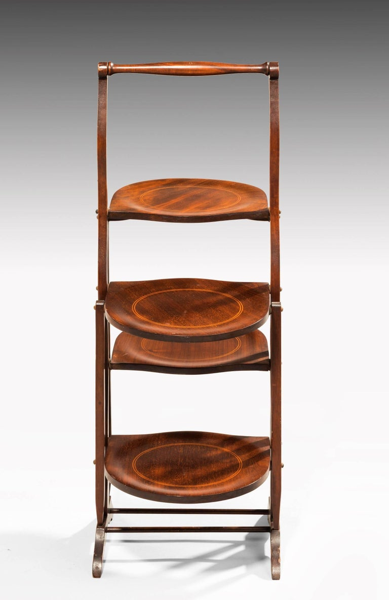 A pretty Edwardian two-sided mahogany folding cake stand. Circular boxwood inlay to all shaped trays.