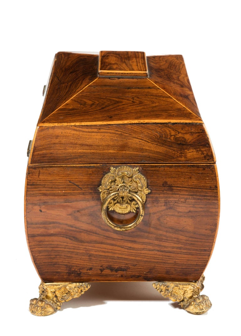 A good Regency period sarcophagus shaped tea caddy. The interior with two fitted lidded compartments but with the central bolt missing. The lid with original pleated silk velvet. Standing on gilt bronze original feet and carrying handles to the