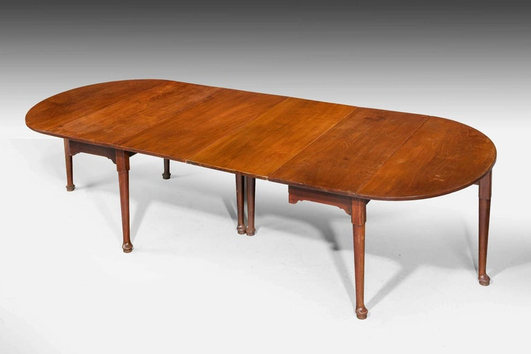 A rare early George III period mahogany dining table, the two end sections with removable leafs. demilune ends, the supports of gentle cabriole form terminating in pad feet. The timbers are beautifully figured and all are in their original