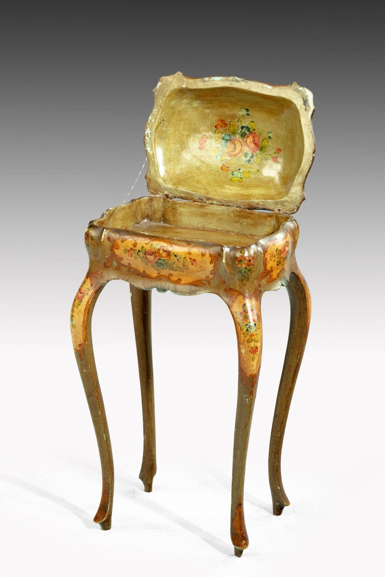 A painted ladies sewing table of exaggerated Bombay form.