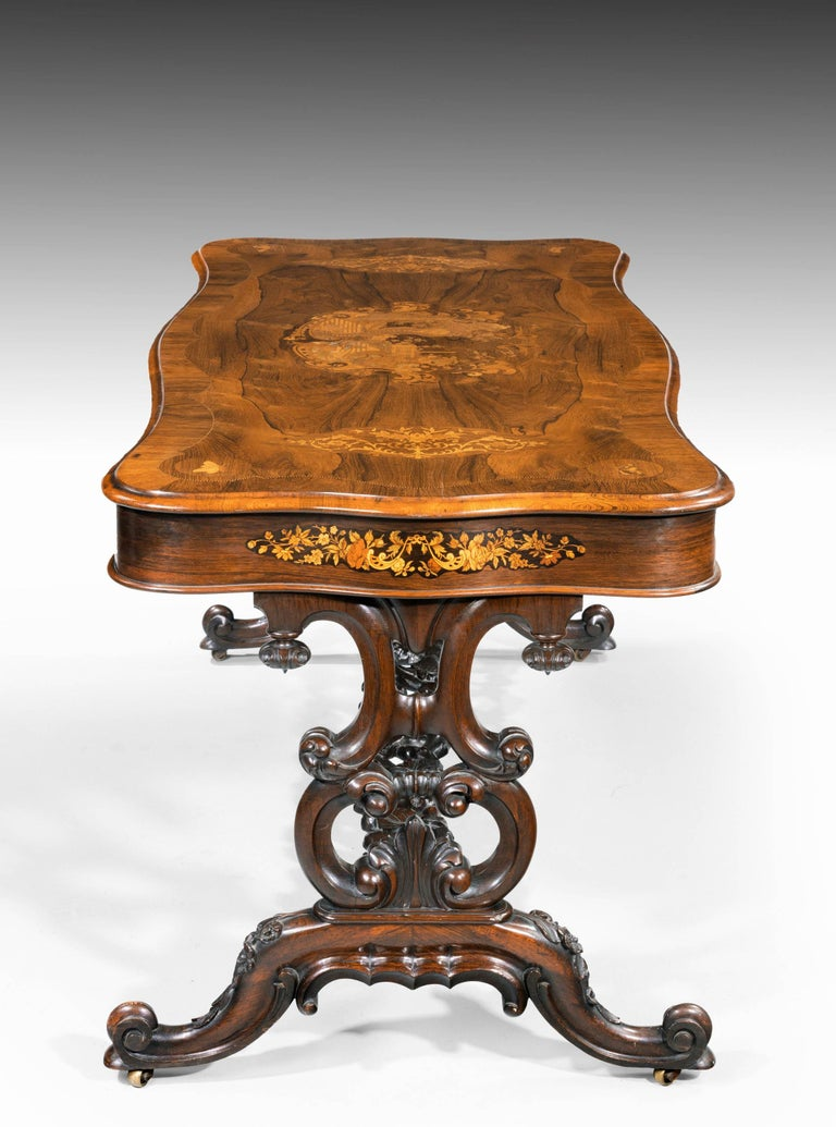 A quite superb 19th century rosewood, kingwood and marquetry center standing table of serpentine outline overall. With a beautifully and elaborately carved stretcher between elegant cabriole supports. The tops and sides of finely executed panels of