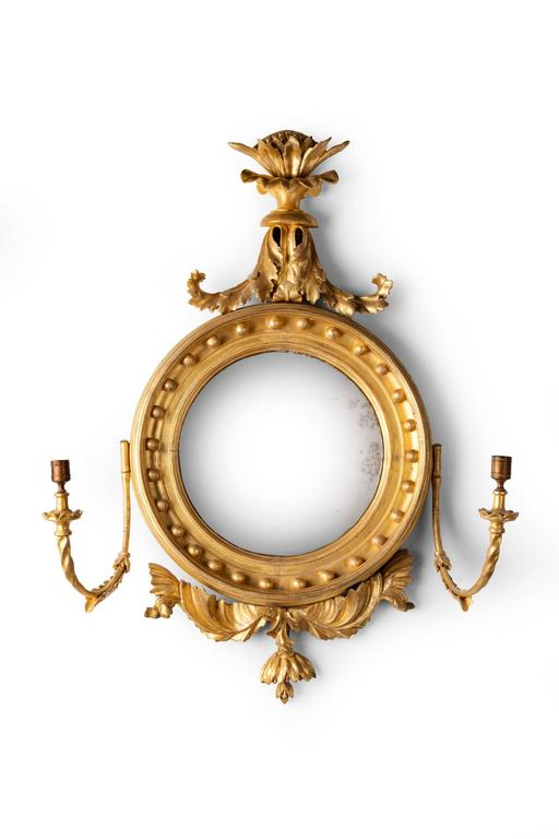 Regency period giltwood convex mirror with girandole candle arms.
