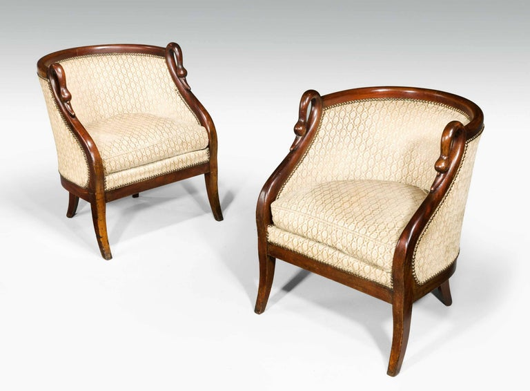 A pair of French mahogany framed armchairs with simulated swans neck uprights, very well figured timber on gentle sabre supports