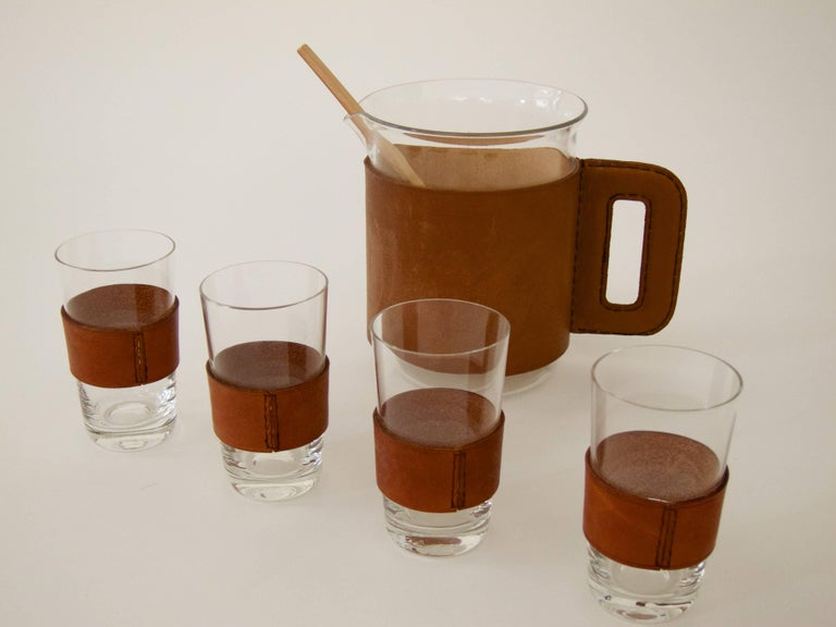 Set of pitcher with four Glasses and a bamboo muddler Handblown glass, leather sleeves (with a leather handle on the pitcher), bamboo muddler Great condition with nice patinated leather.  Pitcher Ø 11.5 cm, H 14.5 cm Glasses Ø 5.5 cm, H 9.8