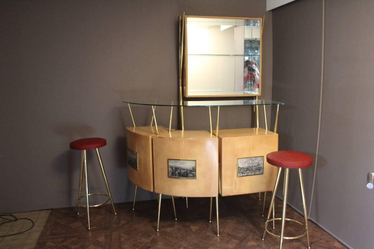 This very chic and complete bar cabinet consists of one high wall-console, one curved serving cabinet and two brass stools with original red moleskine top. The brass base of the console and the cabinet gives a very elegant style to the set. Full