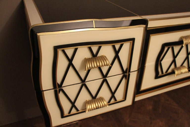 Very refined, this elegant sideboard features an eye-catching geometrical decor made of Murano glass plaques and brass inlay. Black glass segments in relief make crossbars. It has got 2 deep drawers on each side and 2 long drawers in the middle