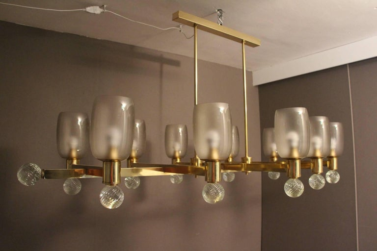 This chandelier has got a very unusual shape since it is slightly oval. It features ten brass arms ending with high grey Murano frozen glass shades and large crystal turned bowls. It is a very architectural chandelier which could be put over a