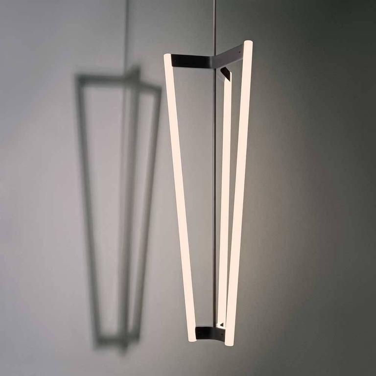 The tube chandelier, a triangular fixture with lights illuminating from each of its three sides, is a sleek addition to any residential or commercial space.  Measures: 12 3/4