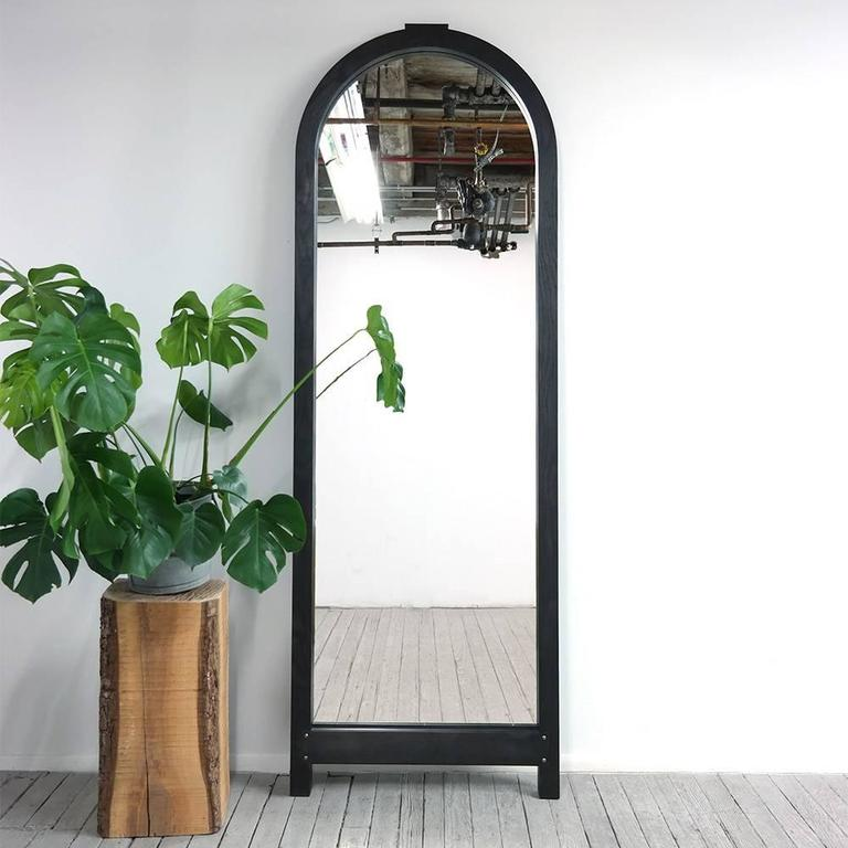 Yucca Stuff's Brazos mirror is dominated by a strong classical arch, which is formed with solid wood voussoirs. To achieve this effect, the mirror was built like a stone arch, and the protruding keystone hints at the method of