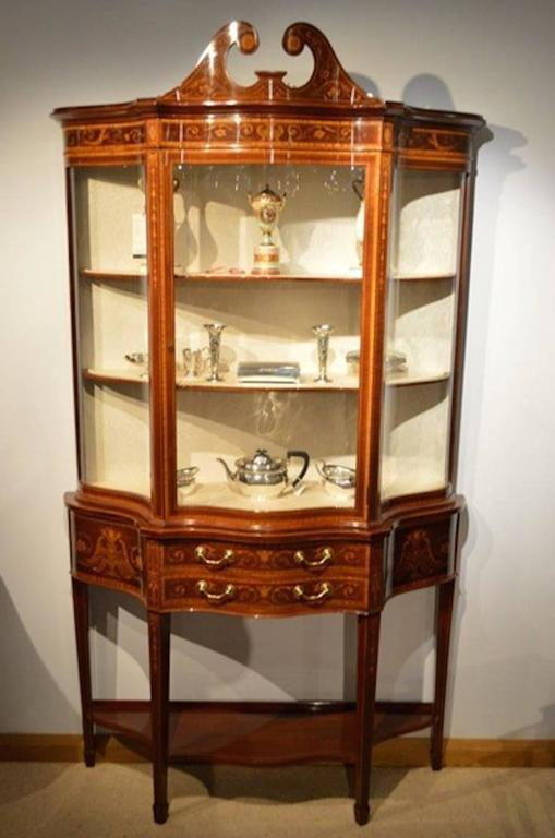 An exhibition quality mahogany inlaid serpentine antique display cabinet by Maple & Co of London. The upper section with a broken swan neck pediment with marquetry inlaid detail and circular paterae above the serpentine frieze depicting mermaids and