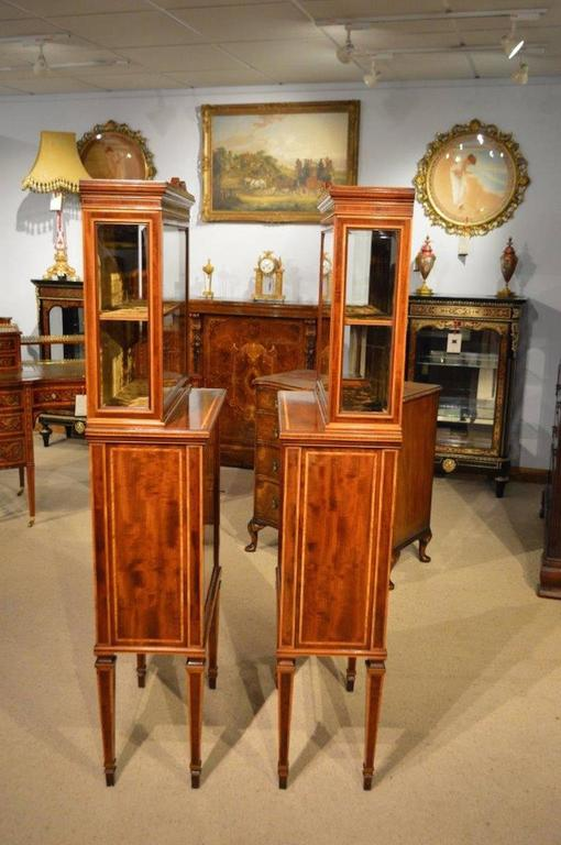 A fine quality pair of Edwardian Period fiddleback mahogany inlaid cabinets. Each with a glazed bevelled glass upper display section with a velvet lined shelved interior and bevelled glazed ends. The lower sections constructed using the finest