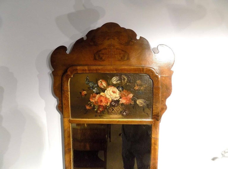 A small walnut Queen Anne style wall mirror. Having a shaped crest veneered in burr walnut above a still life oil painting and rectangular mirror within a walnut frame, English, circa 1900