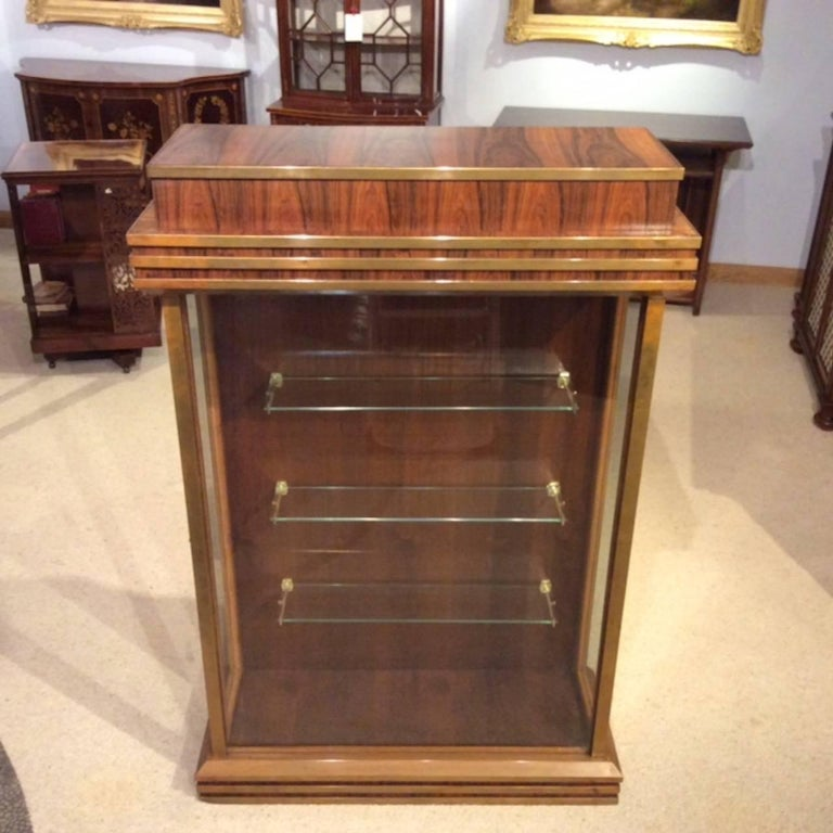 A Fine quality Art Deco Period Rosewood & bronze mounted display cabinet. Having a very stylish Art Deco designed stepped top veneered in beautifully figured rosewood with bronze mounts and having a glazed front with hinged doors to each end to