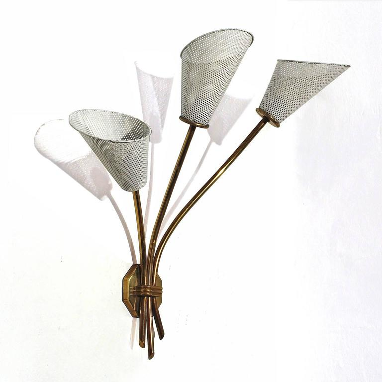 Three light sconce, brass and white lacquered perforated sheet metal or rigitule lampshades (in original condition). In the style of Mathieu Matégot France, circa 1960.