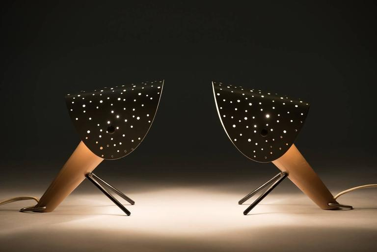 A pair of table or wall lamps. Lacquered metal body with V-shaped lacquered metal legs and lacquered metal shades with pierced holes. Producer: Egon Hillebrand.