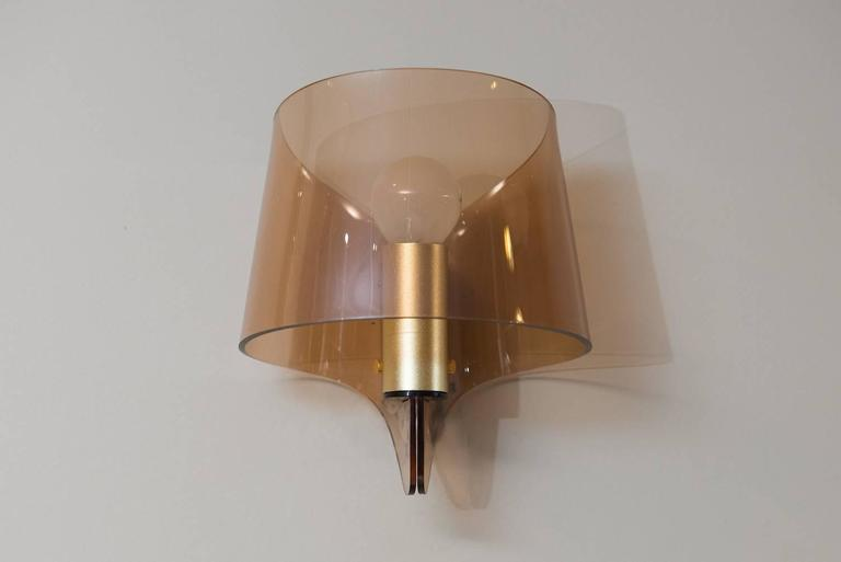 A pair of wall sconces in brass and smoked plexiglass.