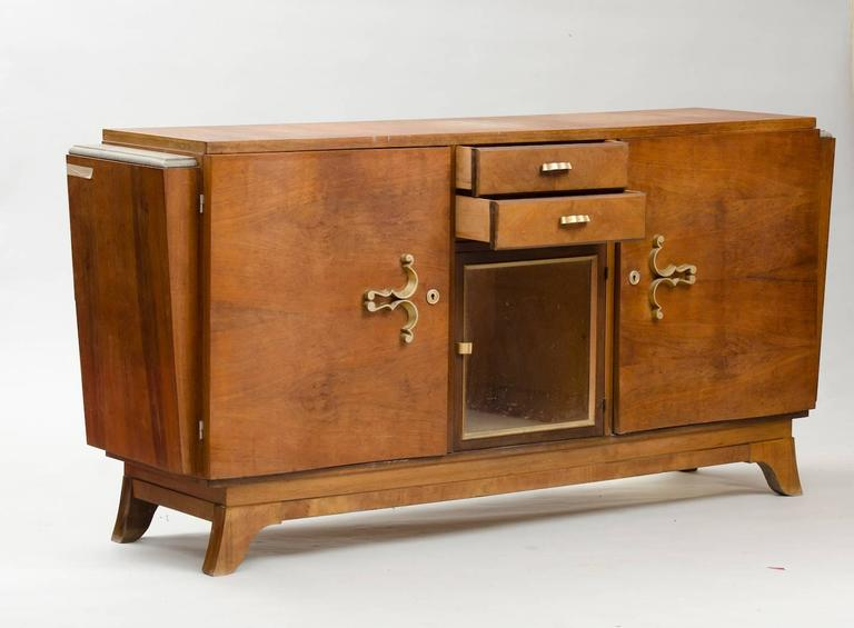 Walnut Art Deco sideboard, with central vitrine and brass hardware. Price fully restored: 3750€ The price shown is in the original condition. We have our own workshop and we can restore these items, including upholstery and all the piece might