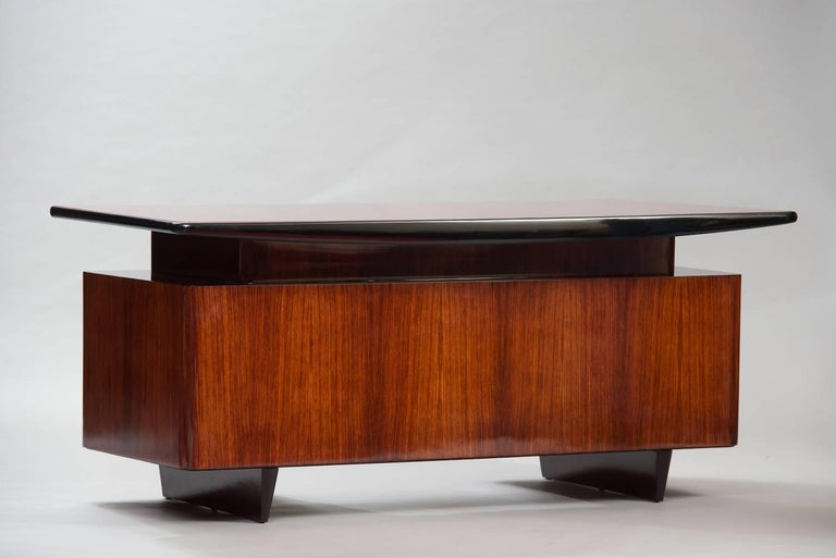 Rosewood desk with bordeaux lacquered glass top.