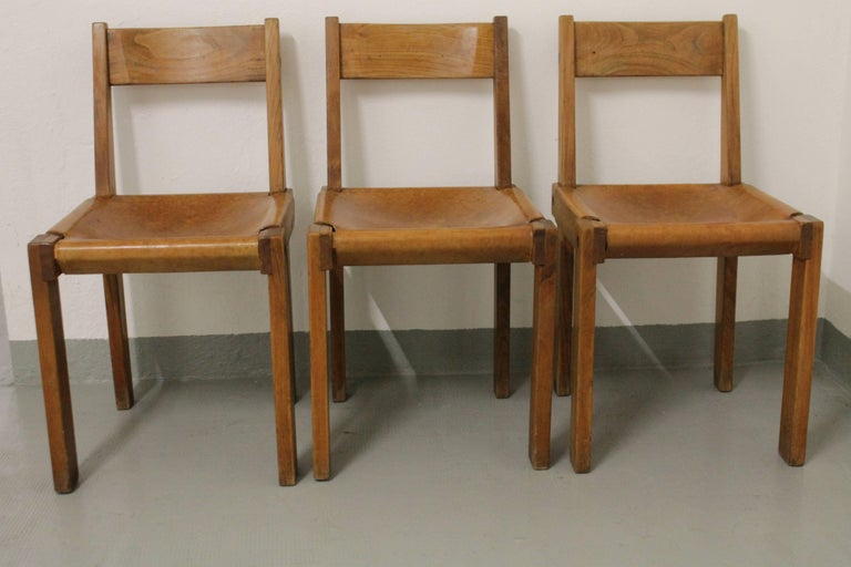 Set of three S24 solid elm and cognac leather dining chairs by Pierre Chapo, France, circa 1960s Beautiful patina, some traces on leather.