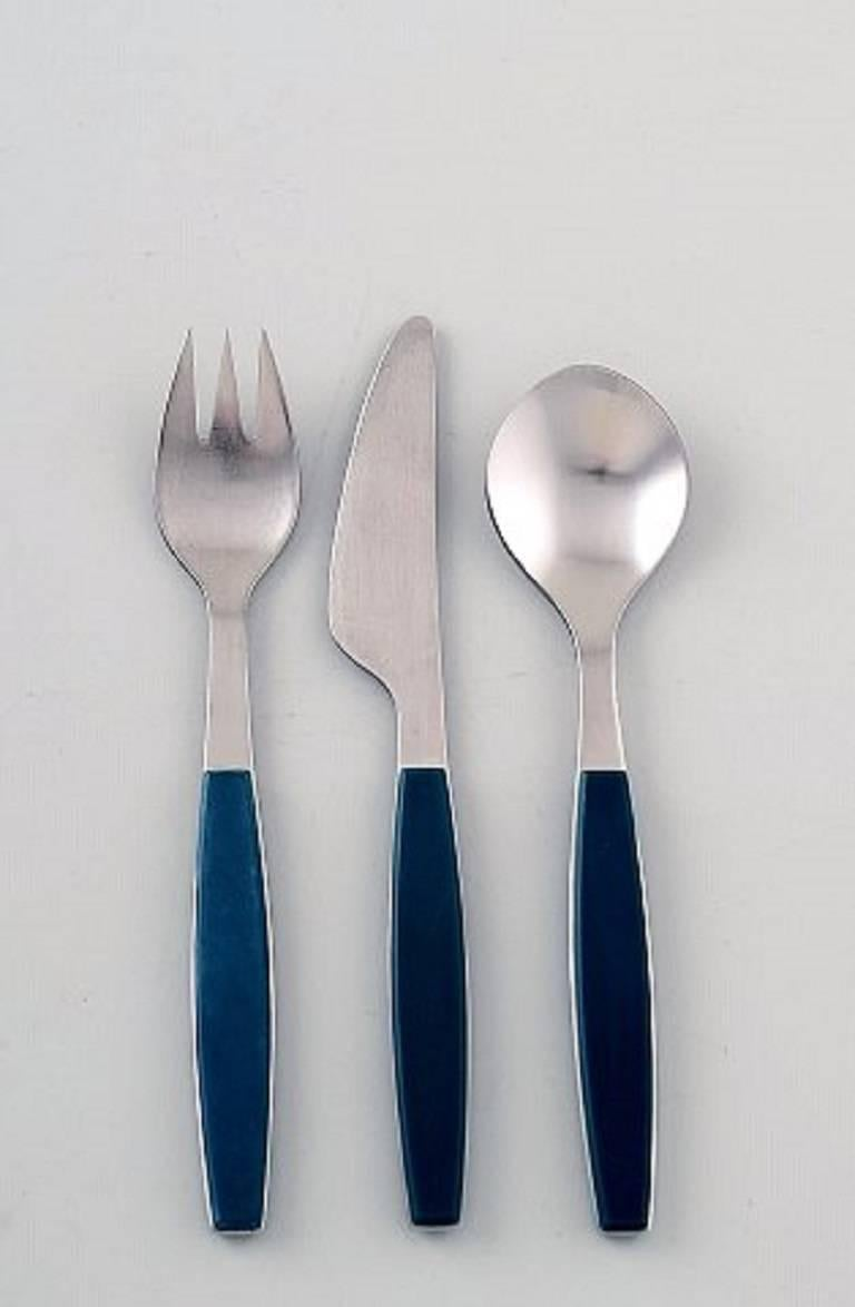 Complete dinner service for six person, Henning Koppel for Georg Jensen. Stainless steel and green plastic cutlery. Manufactured by Georg Jensen. Comprising of: Six dinner knives, six dinner forks, six dinner spoons. In very good