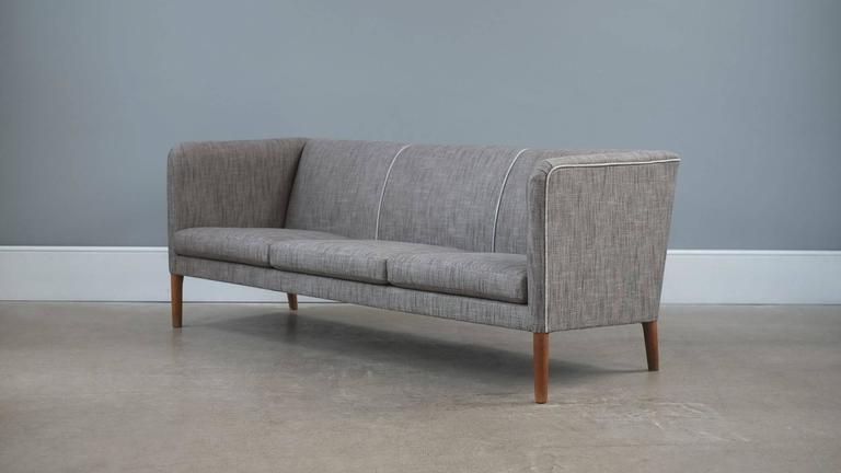 Ultra elegant Even Arm sofa designed by Hans Wegner for cabinet maker AP Stolen, Denmark. Very comfortable sofa fully reconditioned and reupholstered in fabulous grey fabric with contrasting piping details. Great piece.