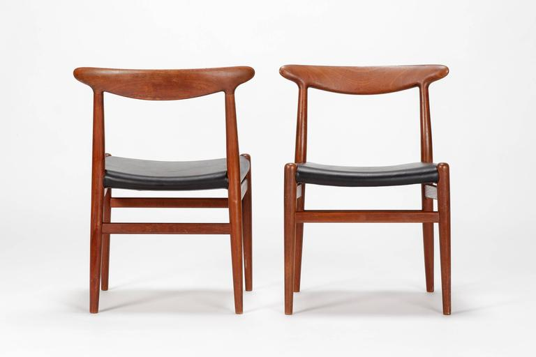 Pair of Hans Wegner chairs, model W2 designed in 1953 and manufactured by C.M. Madsen in Denmark. The frame is made of solid teak wood, the seat covers are made of soft leather. Very typical Wegner shape with round organic elements, solid