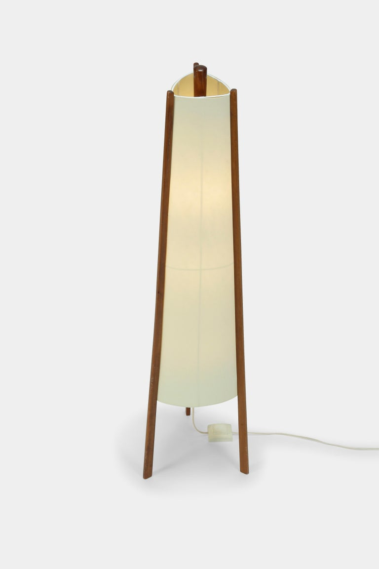 Swiss floor lamp manufactured in the 1950s. New parchment lamp shade attached to three pillars made of solid walnut wood. Generates a pleasant and warm atmosphere.