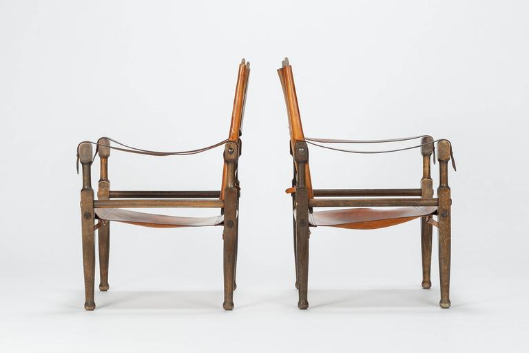 Pair of Swiss design safari chairs, designed by Wilhelm Kienzle in 1928 for Wohnbedarf and manufactured in the 1950s in Switzerland. Frame is made of solid stained beech, covering in original brown leather with a wonderful distinct vintage patina,