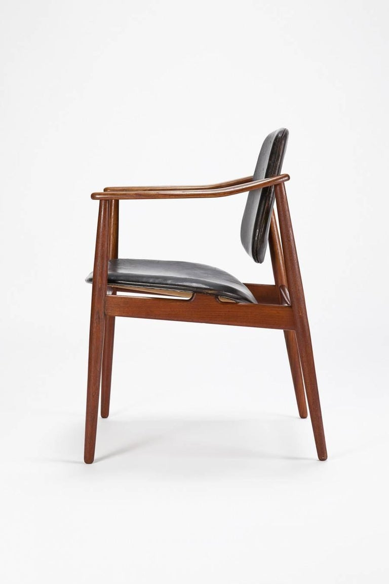 Arne Vodder chair manufactured by Bovirke in Denmark in the 1950s. Seat and back are covered in original black leather and show signs of use and age. The swivel back hardware is made of brass and is attached to the solid teak frame. The pitures are
