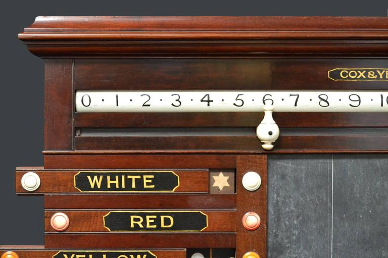 A beautiful mahogany framed scoring cabinet by Cox & Yeman, circa 1860, featuring hand-painted sliding panels, revolving numbers and a central slate panel.  Mr Henry Cox and Mr Edward Yeman joined forces at some time in the 1850s to form their own