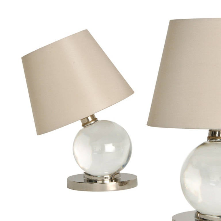 Pair of spherical Baccarat crystal lamps, pivoting on a nickel-plated bronze base. (The crystal globe is not attached to the base in such a way as to make the lamp adjustable).