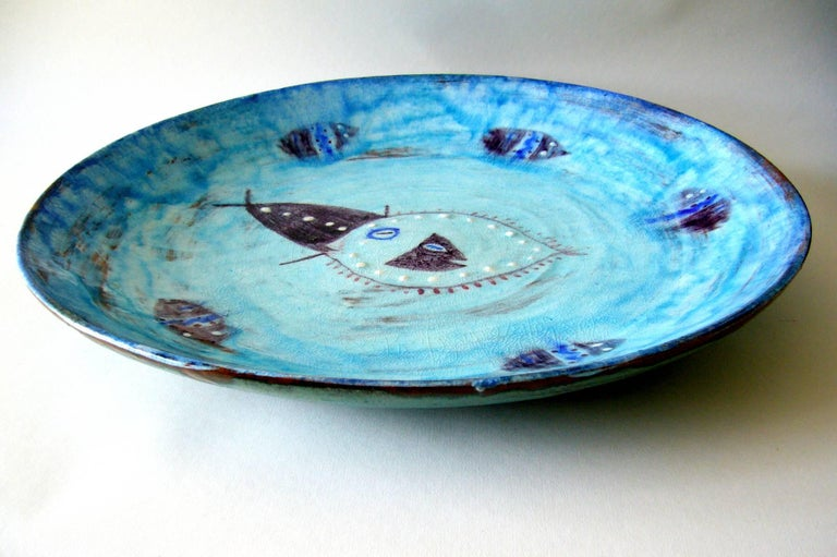 Large-scale ceramic charger with fish motif swimming in an ocean water field. Note the raised white dot embellishment on the fish at centre. Charger measures 16.5