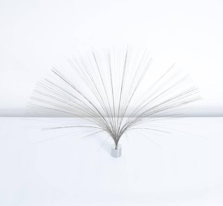 """This dynamic spray sculpture was created by Harry Bertoia and can be dated in the 1960s. The wire """"spray"""" is fixed in a cylindrical chrome base. This mobile sculpture moves through the wind or when you pass by. This sculpture is in good"""