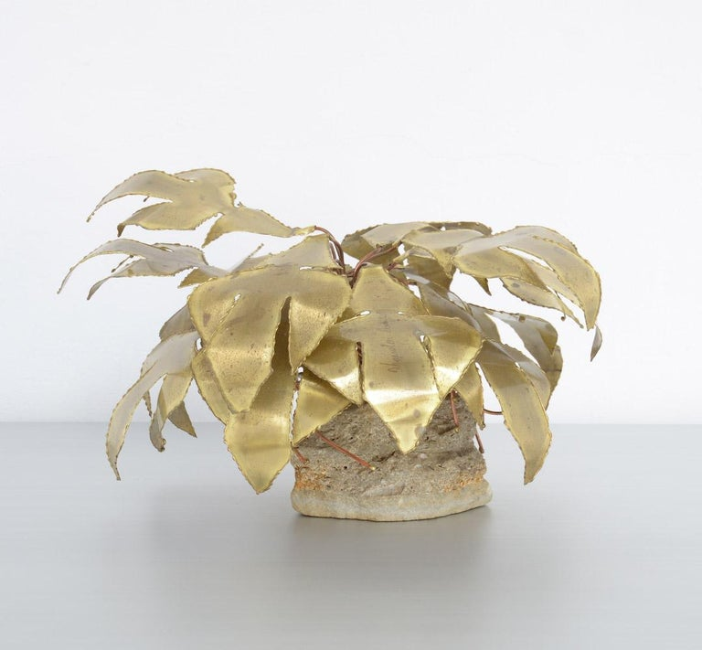 This brass palm tree sculpture was designed and made by Belgian artist Daniel Dhaeseleer in the 1970s. The tree sculpture is made of solid brass and has copper details, it is mounted on a rock base. The artist signed one of the leaves. This