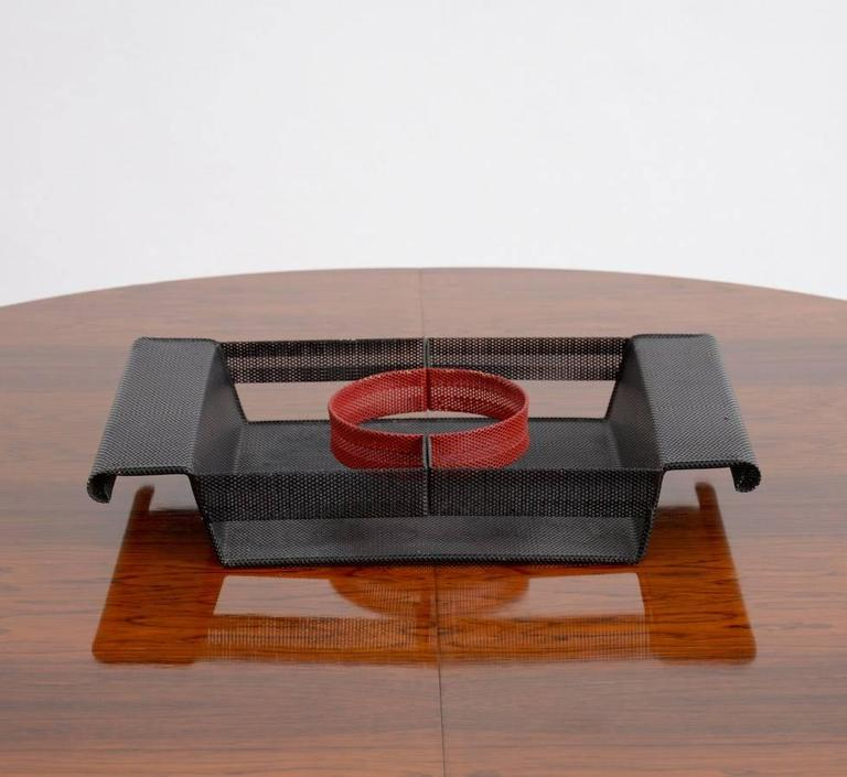 This nice perforated metal serving tray is a great design of the 1950s. It was made in the manner of the work of Mathieu Matégot. The rectangular black lacquered perforated metal tray with a red circular accent is typical for the design of