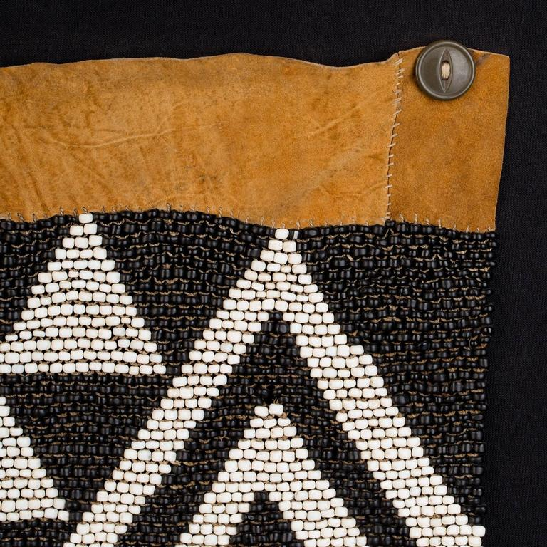 A stunning apron from Botswana, featuring strong geometric designs in dense, graphic sections that seem almost to evoke an abstract landscape with suggestions of mountain, sky, and shadow. Inverting the continuity of black and white at the equator