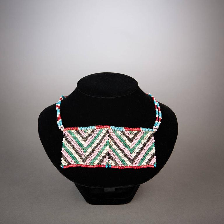 A gorgeous Zulu beaded panel necklace showing excellent preservation. Soft pink and mild green interplay beautifully with black and white in central chevrons lined by red and blue borders.