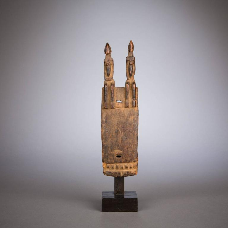 A fine Dogon door lock surmounted by two seated figures. The angular features of the pair are emphasized by strict rectilinear shapes, echoed at the bottom of the lock's face by a strip of projecting squares.